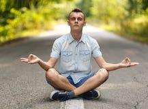 Adolescente que medita en el medio de un camino vacío Foto de archivo libre de regalías