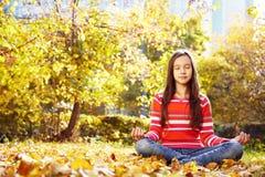Adolescente que medita en el parque del otoño Imágenes de archivo libres de regalías