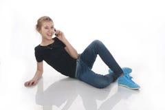 Adolescente que miente abajo hablando en el teléfono Foto de archivo