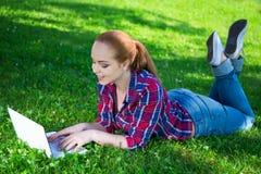 Adolescente que miente con el ordenador portátil en parque Imagen de archivo libre de regalías