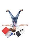 Adolescente que miente con PC, el teléfono y los auriculares de la tablilla sobre whi Fotografía de archivo