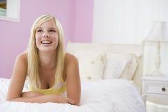 Adolescente que miente en cama Fotos de archivo