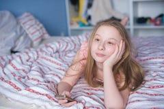 Adolescente que miente en cama con el teléfono Imagen de archivo libre de regalías