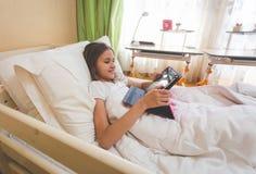 Adolescente que miente en cama en la mañana y que usa la tableta digital Imagen de archivo libre de regalías