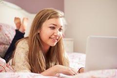 Adolescente que miente en cama usando el ordenador portátil Imagenes de archivo