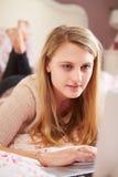 Adolescente que miente en cama usando el ordenador portátil Fotos de archivo
