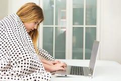 Adolescente que miente en cama usando el ordenador portátil, Fotografía de archivo libre de regalías