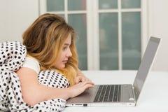 Adolescente que miente en cama usando el ordenador portátil, Fotos de archivo libres de regalías