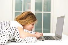 Adolescente que miente en cama usando el ordenador portátil, Foto de archivo