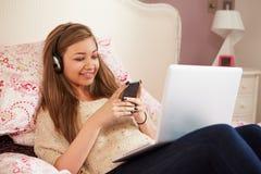 Adolescente que miente en cama usando el ordenador portátil mientras que manda un SMS Imagen de archivo