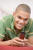 Adolescente que miente en cama usando el teléfono móvil Imagenes de archivo