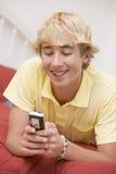 Adolescente que miente en cama usando el teléfono móvil Imágenes de archivo libres de regalías