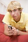 Adolescente que miente en cama usando el teléfono móvil Foto de archivo libre de regalías