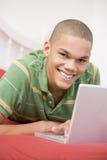 Adolescente que miente en cama usando la computadora portátil Imagen de archivo