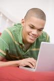 Adolescente que miente en cama usando la computadora portátil Foto de archivo libre de regalías