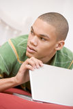 Adolescente que miente en cama usando la computadora portátil Imagen de archivo libre de regalías