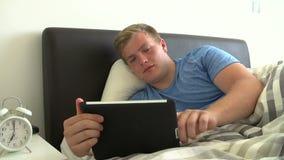 Adolescente que miente en cama usando la tableta de Digitaces almacen de video