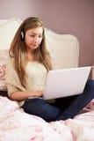 Adolescente que miente en cama usando los auriculares que llevan del ordenador portátil Foto de archivo