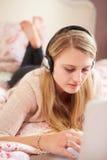 Adolescente que miente en cama usando los auriculares que llevan del ordenador portátil Fotografía de archivo