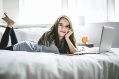 Adolescente que miente en cama usando un ordenador portátil Foto de archivo libre de regalías