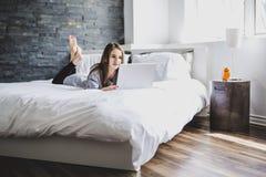 Adolescente que miente en cama usando un ordenador portátil Imagen de archivo libre de regalías