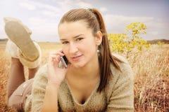 Adolescente que miente en campo usando un teléfono móvil Imagen de archivo