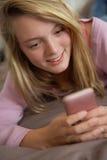 Adolescente que miente en dormitorio usando el teléfono móvil Foto de archivo