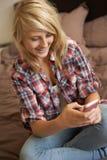 Adolescente que miente en dormitorio usando el teléfono móvil Imágenes de archivo libres de regalías