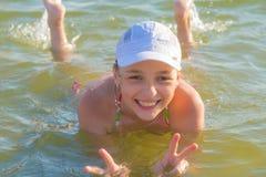 Adolescente que miente en el agua en el lago Fotos de archivo libres de regalías