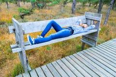 Adolescente que miente en el banco en bosque Foto de archivo libre de regalías
