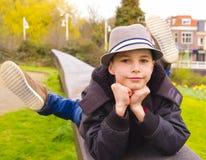 Adolescente que miente en el parapeto en el parque Fotos de archivo libres de regalías
