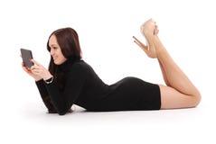 Adolescente que miente en el piso que mira la PC de la tableta Foto de archivo libre de regalías