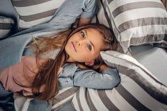 Adolescente que miente en el sofá en una sala de estar Fotografía de archivo