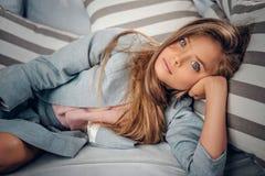 Adolescente que miente en el sofá en una sala de estar Fotos de archivo
