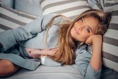 Adolescente que miente en el sofá en una sala de estar Foto de archivo