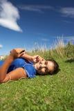 Adolescente que miente en hierba con el jugador mp3 Imagen de archivo libre de regalías