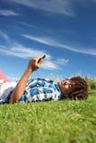 Adolescente que miente en hierba con el teléfono Fotos de archivo libres de regalías