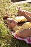 Adolescente que miente en hierba con el teléfono Imagenes de archivo