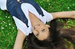 Adolescente que miente en hierba con las flores Imagenes de archivo