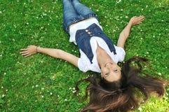 Adolescente que miente en hierba con las flores Imagen de archivo libre de regalías
