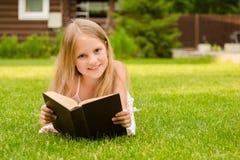 Adolescente que miente en hierba y el libro leído Imagen de archivo libre de regalías