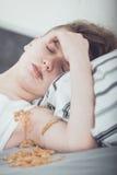 Adolescente que miente en la cama cubierta en vómito Foto de archivo libre de regalías