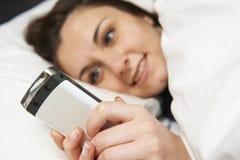 Adolescente que miente en la cama que envía el mensaje de texto Imagen de archivo