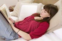 Adolescente que miente en la cama que lee un libro Fotografía de archivo