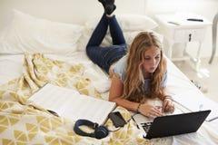 Adolescente que miente en la cama que trabaja con el ordenador portátil, alto ángulo Fotografía de archivo libre de regalías
