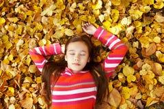 Adolescente que miente en las hojas amarillas Imagen de archivo
