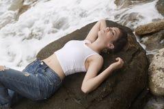Adolescente que miente en las rocas Fotos de archivo libres de regalías