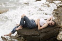 Adolescente que miente en las rocas Fotografía de archivo