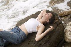 Adolescente que miente en las rocas Imagen de archivo libre de regalías