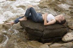 Adolescente que miente en las rocas Foto de archivo libre de regalías